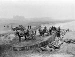 Workmen, horses and carts constructing sea defences in 1910