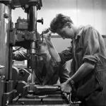Apprentice worker using an industrial drill at a workshop in Glasgow