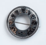 Silver brooch set with granite
