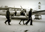 Ambulance flight at Barra airstrip with patient and nurse being carried on board c1960