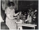 Agnes Innes checking bottled fruit in the caravan 'Golden Eagle', before 1954