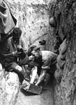 British soldiers cleaning equipment in a trench. Western Front, France, c.1916-1918