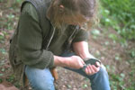 Photograph, of making an arrowhead with an antler shaping tool