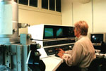 Photograph, of conservator using a scanning electron microscope to examine objects from hoard