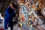 Conservator, Alan Simpson, re-gilding George II's coat of arms set over the principal gate at Fort George
